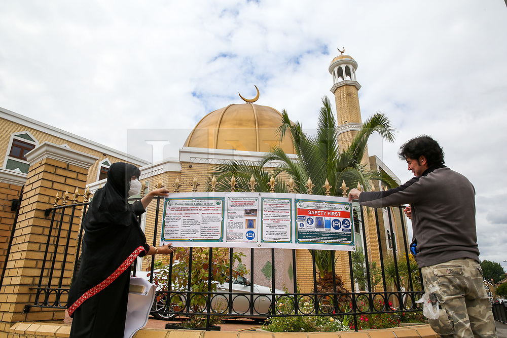 © Licensed to London News Pictures. 06/07/2020. London, UK. Mrs Bibi Khan, president of London Islamic Cultural Society and Mosque and a member of staff wearing face coverings displays a sign on the railing of the Mosque. Wightman Road Mosque, also known as London Islamic Cultural Society and Mosque, in north London, prepares to open after the COVID-19 lockdown, by placing a number of measures required by law for worshippers. The government announced that gatherings of more than 30 worshippers are allowed for acts of communal worship in churches, synagogues, mosques, temples and other places of worship. All worshippers attending Mosques will have to wear face coverings and bring their own prayer mat, Quran, and a reusable shoe bag. Photo credit: Dinendra Haria/LNP