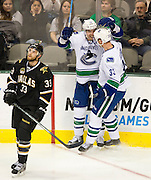 Henrik Sedin (33) of the Vancouver Canucks celebrates after scoring a goal with teammate Alexandre Burrows (14) while Alex Goligoski (33) of the Dallas Stars watches the replay on the big screen Thursday, February 21, 2013 at the American Airlines Center in Dallas, Texas. (Cooper Neill/The Dallas Morning News)