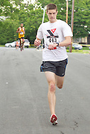 Middletown, New York - David McCarey of Circleville checks his watch as the nears the finish line in the 16th annual Ruthie Dino-Marshall 5K Run/Walk put on by the Middletown YMCA on Sunday, June 10, 2012. McCarey won the race in 16 minutes, 28 seconds.
