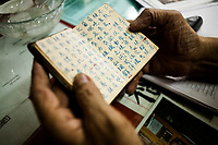 An elder herbalist looks through a recipe book filled with Chinese characters in Hanoi, Vietnam.