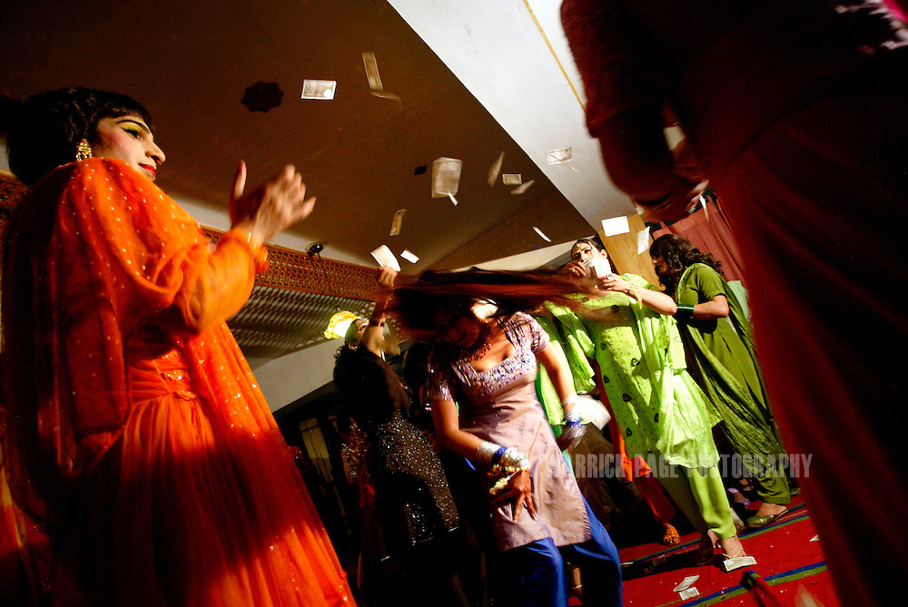 """Hijras (eunuchs) throw money over a dancer during an underground party, June 16, 2005, Rawalpindi, Pakistan. The suspected hideout of Osama Bin Laden, Al Qaeda leaders and countless Islamic militants, Pakistan is also home to one of the subcontinents largest communities of transsexuals, eunuchs and transvestites, or as they are more commonly known - Hijras. Caught between modernity and fundamentalism at the frontline in the war against terror, the Islamic Republic is a country at war with its own identity, yet its Kushras (Urdu for eunuch) stand out as a tight-nit community of devout Muslims. As Pakistan's most marginalised community, they live in fear """"24 hours a day"""", according to the group She-male Rights of Pakistan. Hijras are considered by many as unclean, amoral, drug users, and who also have the ability to place curses. Many people fear their curse so gravely, they will give generously when a Kushra comes to beg in their neighbourhood and ask them for Allah's blessing.. (Photo by Warrick Page)"""