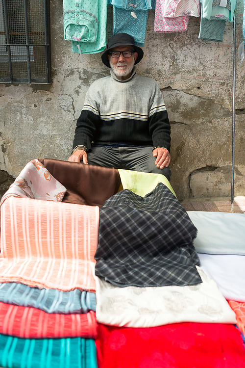 TETOUAN, MOROCCO - 5th April 2016 - Portrait of a clothing items and fabrics seller sitting at his stall in the Tetouan Medina, Rif region of Northern Morocco.