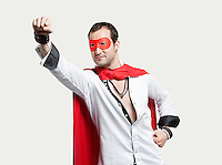 Young man wearing superhero costume against gray background