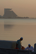 The landmark pyramid of Sheraton Doha hotel at dawn. Muslims coming back from morning prayer at the corniche.
