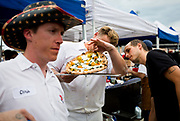 Derek Lee, owner and pizzaoilo of Pizza Bruta, checks on the crust of pizza during the 4th annual Yum Yum Fest held at Breese Stevens Field, Sunday, August 6, 2017.