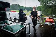 Foto: Gerrit de Heus. Emmen. 13-06-2015. Armand en The Kik op Retropop. In de stromende regen brengt zanger Dave von Raven (R) de apparatuur het podium op.