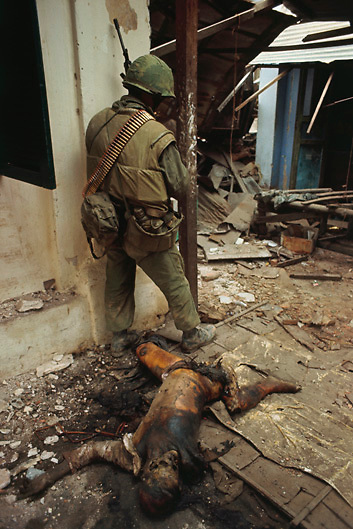 tet Offensive inside city of Hue: Hue, South Vietnam:  The charred remains of a Viet Cong soldier lie amid rubble in street where a U.S. Marine stands on the alert for further confrontations with Communist forces. February 17, 1968 Hue, South Vietnam