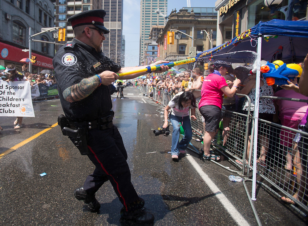 Toronto, Ontario ---2014-06-29--- A Toronto Police Officer  engages spectators in a water gun fight along the parade route as he marches in the World Pride parade in Toronto, Ontario, Canada, June 29, 2014 .<br /> GEOFF ROBINS AFP