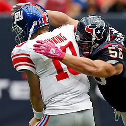 October 10, 2010; Houston, TX USA; Houston Texans linebacker Brian Cushing (56) hits New York Giants quarterback Eli Manning (10) following a pass during the second half at Reliant Stadium. The Giants defeated the Texans 34-10. Mandatory Credit: Derick E. Hingle