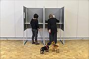 Nederland, Ubbergen, 18-3-2015Verkiezingen voor de provinciale staten, en indirect voor de eerste kamer. Twee vrouwen met hondjes staan gelijktijdig in een stemhokje.Netherlands, elections. Dit stembureau staat in een dorpshuis. Stembureau, stemburo in een buurthuis. Netherlands, elections voting . Polling station Foto: Flip Franssen/Hollandse Hoogte
