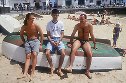 Group of young men sitting on upturned boat on beach,