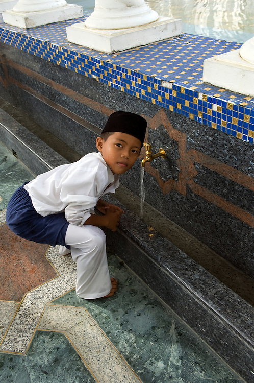 """Moslem boy in  """"friday best"""" attend prayers at the Omar Ali Saifuddien Mosque"""