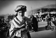 Elder Kabuli man shopping in Kabul riverfront market in front of Murad Khane, Kabul, Afghanistan.