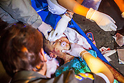 "10 NOVEMBER 2012 - BANGKOK, THAILAND: A Ruamkatanyu Foundation medical team cleans the face of a boy who died after being hit by a vehicle near the Klong Toey slum in Bangkok. Medics worked on the child for nearly 30 minutes and were not able to revive him. The child had severe head injuries and died at the scene. The Ruamkatanyu Foundation was started more than 60 years ago as a charitable organisation that collected the dead and transported them to the nearest facility. Crews sometimes found that the person they had been called to collect wasn't dead, and they were called upon to provide emergency medical care. That's how the foundation medical and rescue service was started. The foundation has 7,000 volunteers nationwide and along with the larger Poh Teck Tung Foundation, is one of the two largest rescue services in the country. The volunteer crews were once dubbed Bangkok's ""Body Snatchers"" but they do much more than that now.    PHOTO BY JACK KURTZ"