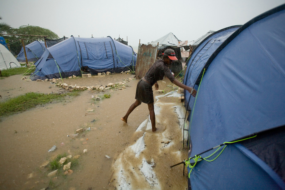 Roseline Dorse closes her tent door during the rain in her flooding camp. Dorse and her family were displaced by the January earthquake.