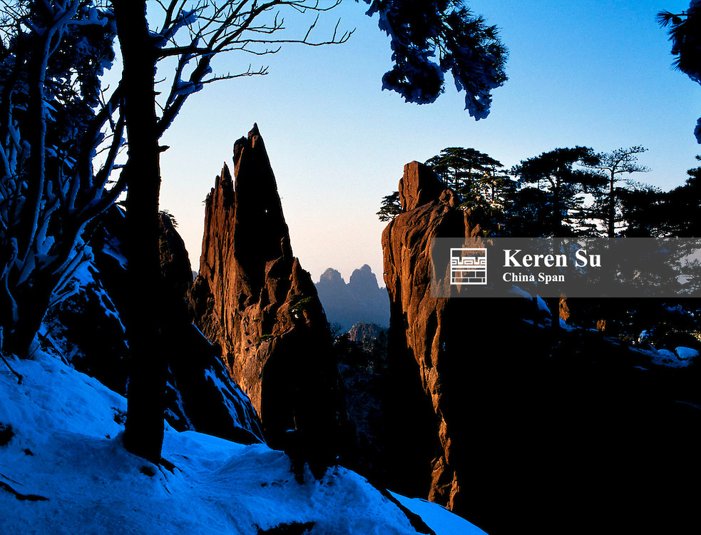 Pine trees and huge rocks on snow, Mt. Huangshan (Yellow Mountain), Anhui Province, China