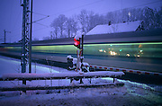 As blue light fades on a bitterly cold winter's evening, the barrier of an Austrian level-crossing has been lowered to stop traffic and allow a high-speed ICE-T train to continue on its route through, near Salzburg, Austria, Europe. OBB, the Austrian Federal Railways operate a network of 5,683 km makes them the by far largest railway-company in this country. Heavy snow has fallen in this region of the Alps and deposits have settled on the fences and the glowing red stop traffic light, signalling for motorists to halt at this dangerous road-crossing location. So fast is this mode of transport, it blurs past this cold, desolate spot where only one nearby house is next to the trackside. (From a story about travelling through 6 European countries by coach in 7 days).