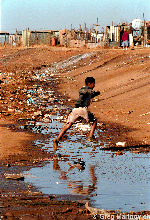 IPMG0340 South Africa, Bekkersdal, 1994:.A boy leaps over a polluted stream in Mandela Park squatter camp, Bekkersdal township west of Johannesburg, South Africa. 1994. Access to water is one of Africa's most pressing needs..Photograph by Greg Marinovich/South Photographs