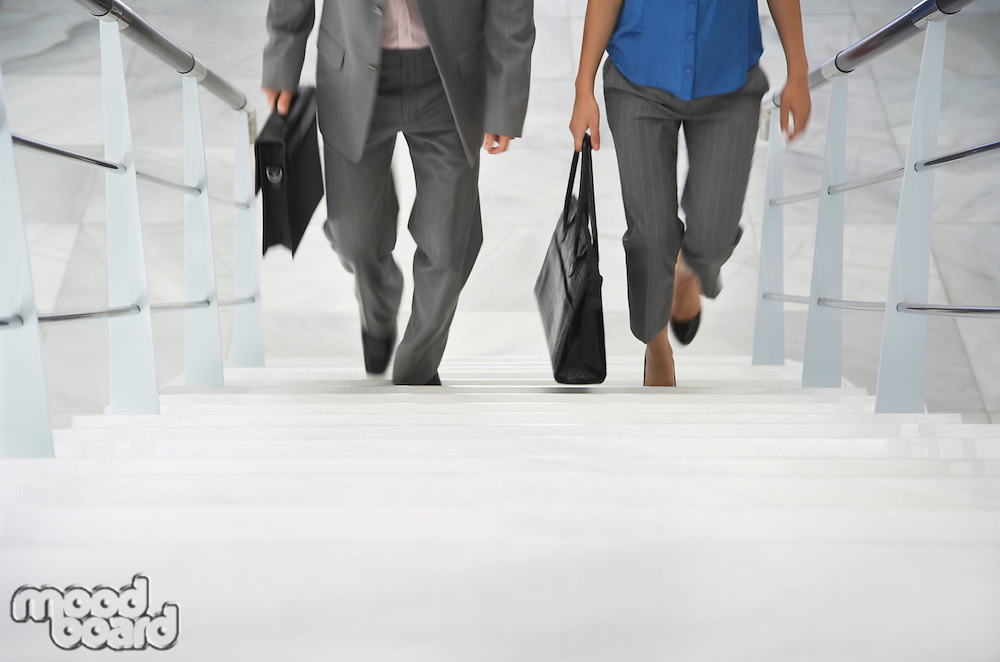Two business people walking up stairs
