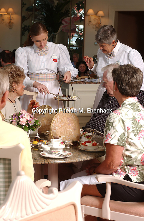 Restaurant servers show patrons some of the desserts available for the afternoon tea at the Grand Floridian Hotel at the Walt Disney World Resort in Lake Buena Vista, Florida.