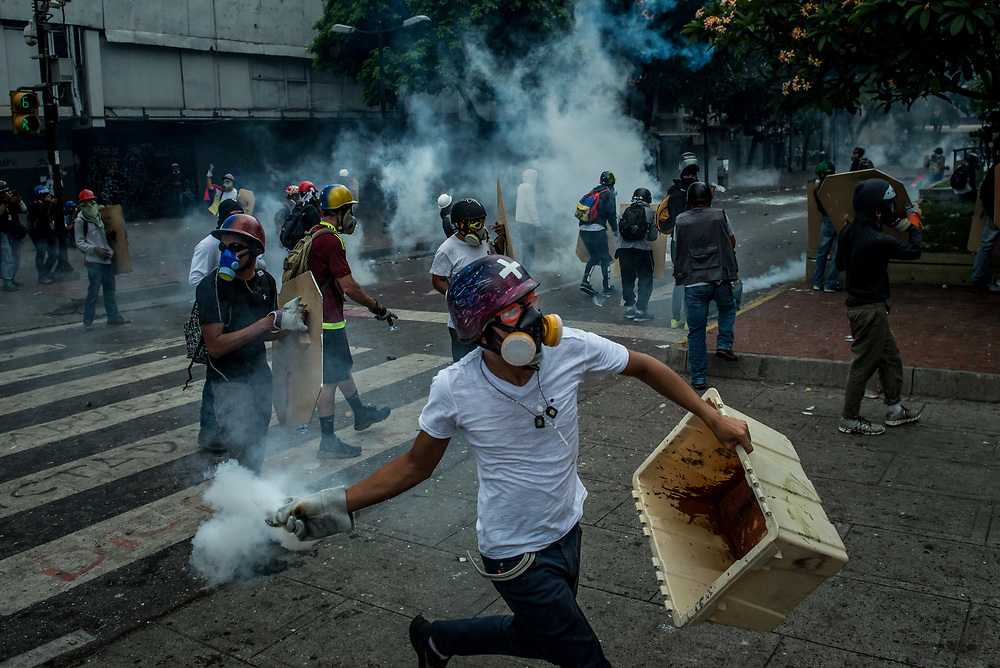 CARACAS, VENEZUELA - MAY 8, 2017: An anti-government protester throws a tear gas canister back at members of the National Police, who had previously shot it at a group of protesters during clashes in Caracas. The streets of Caracas and other cities across Venezuela have been filled with tens of thousands of demonstrators for nearly 100 days of massive protests, held since April 1st. Protesters are enraged at the government for becoming an increasingly repressive, authoritarian regime that has delayed elections, used armed government loyalist to threaten dissidents, called for the Constitution to be re-written to favor them, jailed and tortured protesters and members of the political opposition, and whose corruption and failed economic policy has caused the current economic crisis that has led to widespread food and medicine shortages across the country.  Independent local media report nearly 100 people have been killed during protests and protest-related riots and looting.  The government currently only officially reports 75 deaths.  Over 2,000 people have been injured, and over 3,000 protesters have been detained by authorities.  PHOTO: Meridith Kohut