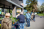 People are waiting in front of a shop in Oberhöchstadt in times of social distancing because of the corona virus.
