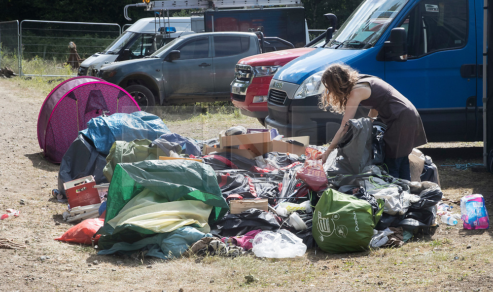 © Licensed to London News Pictures. 23/06/2017. Dorking, UK. A protestor collects her belongings as workers dismantle a protest fort built over an oil well site near Leith Hill in the North Downs . Protestors have been evicted from the camp over the last few days. Planning permission for 18 weeks of exploratory drilling was granted to Europa Oil and Gas in August 2015 after a four-year planning battle. The camp was set up by protestors in October 2016 in order to draw attention to plans to drill in this Area of Outstanding Natural Beauty (AONB) in the Surrey Hills. The camp has received support from the local community. Photo credit: Peter Macdiarmid/LNP
