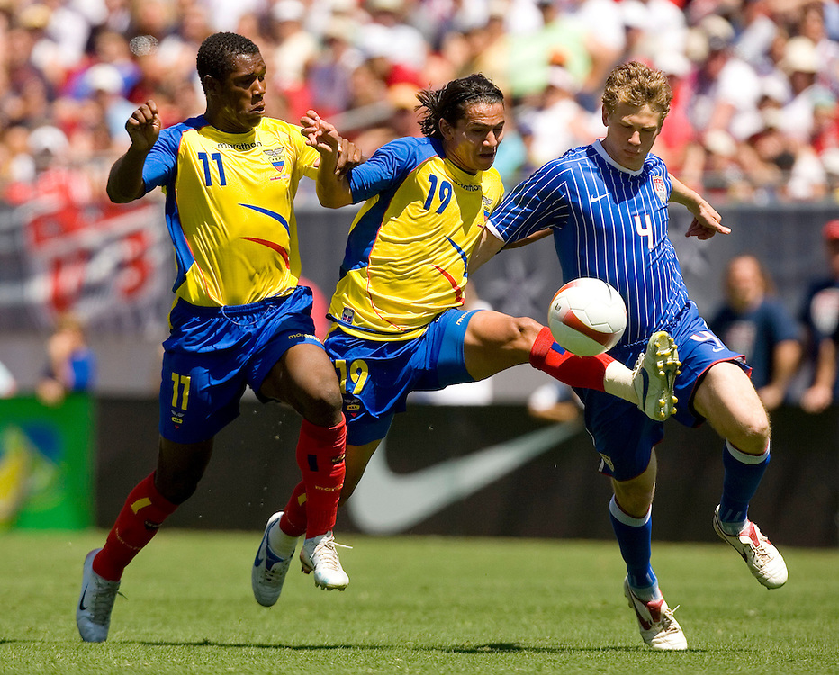 Ecuador's Luis Saritama (C) pushes between teammate Edmundo Zura (L) and the United States' Jonathan Spector (R) while trying to move up the ball up the field during the second half of their international friendly soccer match in Tampa, Florida March 25, 2007. REUTERS/Scott Audette (UNITED STATES)