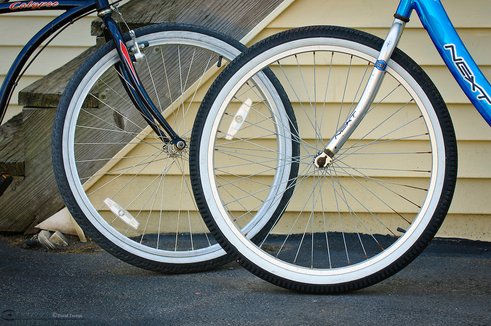 Front wheels of two beach bicycles.