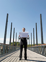 Young business man standing on bridge holding papers