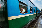 15 JUNE 2013 - YANGON, MYANMAR:  A boy looks out the window of the Yangon Circular Train. The Yangon Circular Railway is the local commuter rail network that serves the Yangon metropolitan area. Operated by Myanmar Railways, the 45.9-kilometre (28.5mi) 39-station loop system connects satellite towns and suburban areas to the city. The railway has about 200 coaches, runs 20 times and sells 100,000 to 150,000 tickets daily. The loop, which takes about three hours to complete, is a popular for tourists to see a cross section of life in Yangon. The trains from 3:45 am to 10:15 pm daily. The cost of a ticket for a distance of 15 miles is ten kyats (~nine US cents), and that for over 15 miles is twenty kyats (~18 US cents). Foreigners pay 1 USD (Kyat not accepted), regardless of the length of the journey.    PHOTO BY JACK KURTZ