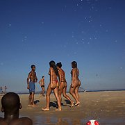 Locals stop playing football as a group of girls walk past in the late afternoon light at Sao Conrado beach, Rio de Janeiro,  Brazil. 8th July 2010. Photo Tim Clayton..The beaches of Rio de Janeiro, provide the ultimate playground for locals and tourists alike. Beach activity is in abundance as beach volley ball, football and a hybrid of the two, foot volley, are played day and night along the length and breadth of Rio's beaches. .Volleyball nets and football posts stretch along the cities coastline and are a hive of activity particularly at it's most famous beaches Copacabana and Ipanema. .The warm waters of the Atlantic Ocean provide the ideal conditions for a variety of water sports. Walkways along the edge of the beaches along with exercise stations and cycleways encourage sporting activity, even an outdoor gym is available at the Parque Do Arpoador overlooking the ocean. .On Sunday's the main roads along the beaches of Copacabana, Leblon and Ipanema are closed to traffic bringing out thousands of people of all ages to walk, run, jog, ride, skateboard and cycle more than 10 km of beachside roadway. .This sports mad city is about to become a worldwide sporting focus as they play host to the world's biggest sporting events with Brazil hosting the next Fifa World Cup in 2014 and Rio de Janeiro hosting the Olympic Games in 2016...