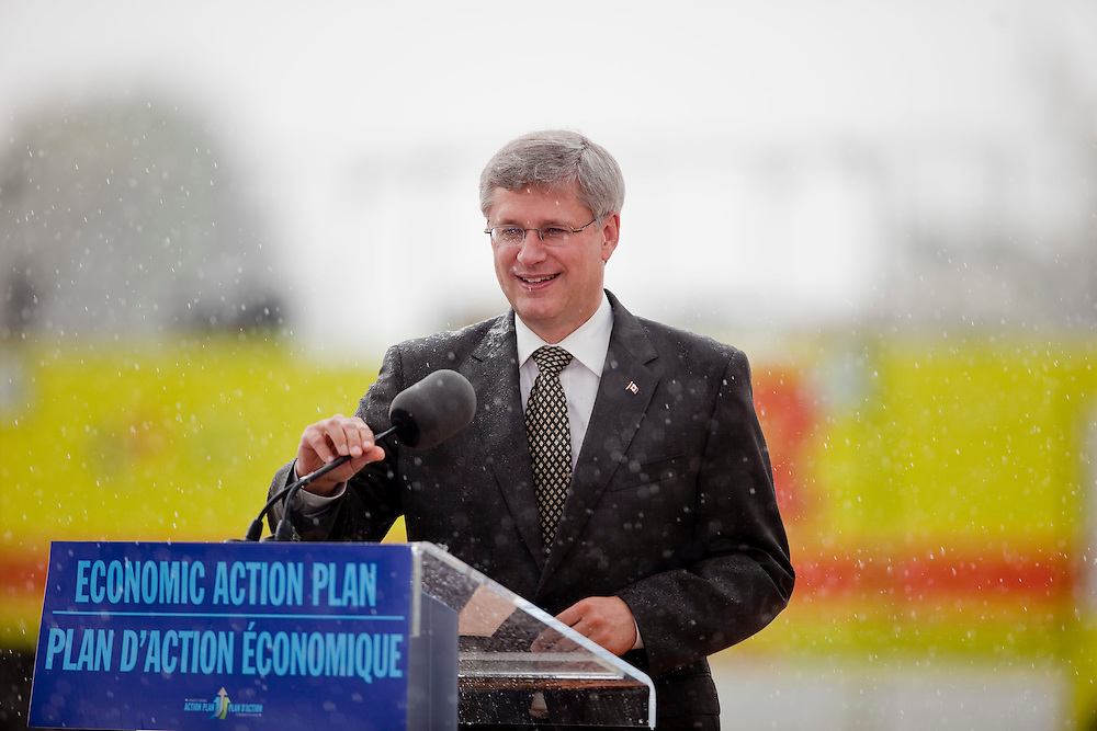 Prime Minister Stephen Harper smiles as he is caught in a downpour at the opening of the Foreign Trade Cargo Complex at the London International Airport, in London, Ontario, September 2, 2010.<br /> REUTERS/Geoff Robins