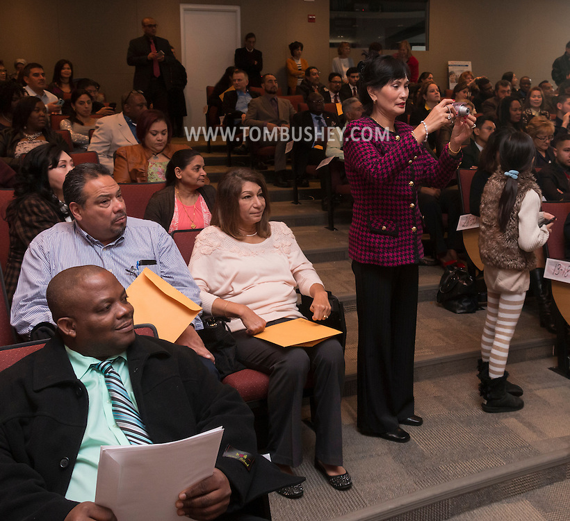Goshen, New York - A woman takes a photograph during a Naturalization ceremony at the Orange County Emergency Services Center on Nov. 17, 2016.
