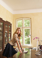 Young woman leaning on table in living room