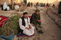 Inmates sit in the 40ft square courtyard of the ir prison in Tirin Kot, the capital of Oruzgan province. Guards said there are 96 prisoners in a jail meant for just 35. Prisoners sleep shoulder to shoulder on blankets on the floor. The governor, Haji Bismillah, said they live like animals.