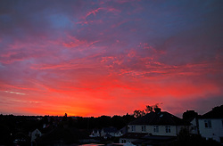 ©Licensed to London News Pictures 31/07/2020     Orpington, UK. The sun sets on the third hottest day in the UK ever, leaving a bright red sky mixed in with dark clouds over Orpington in South East London. Photo credit: Grant Falvey/LNP