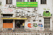 KUALA LUMPUR, MALAYSIA - AUGUST 29, 2009: Unidentified man stands at the restaurant entrance at the backstreet in Kuala Lumpur, Malaysia.
