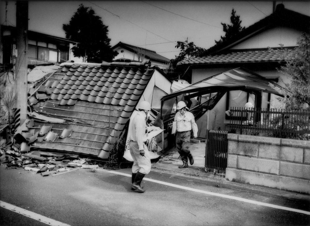 Workers from Taisei Corporation survey a property in central Odaka to determine how much radiation decontamination will be needed to make this earthquake-damage house suitable for human habitation.  According to a 10 February 2012 New York Times article three large construction companies that actually helped build 45 out of Japan's 54 nuclear reactors, Taisei is one of the them, have received large contracts to decontaminate towns and villages fouled by fallout in Fukushima Prefecture despite not having any experience in decontamination work.   Critics say this highlights the uncomfortably close ties between Japan's nuclear industry and the central government...Odaka used to be inside the nuclear no-entry zone until the government pushed the line back from 20 km (12.4 miles) to roughly 12 kilometers (9.3 miles) on the northern and southern coastline portions in April 2012.  Odaka, Fukushima Prefecture, Japan..