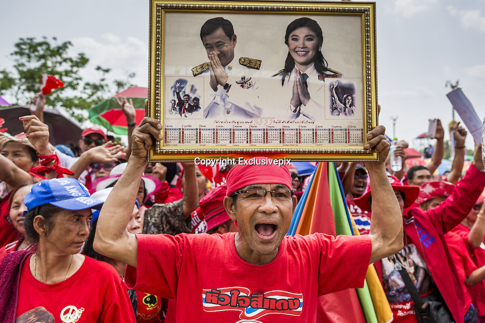April 6, 2014 - Bangkok, Bangkok, Thailand - <br /> <br /> Red Shirts Rally in Bangkok Suburbs<br /> <br /> A man holds up photos of Thaksin Shinawatra, the exiled former Prime Minister of Thailand and Yingluck Shinawatra, the current Prime Minister and Thaksin's sister. Red Shirts and supporters of the government of Yingluck Shinawatra, the Prime Minister of Thailand, gathered in a suburb of Bangkok this weekend to show support for the government. The Thai government is dealing with ongoing protests led by anti-government activists. Legal challenges filed by critics of the government could bring the government down as soon as the end of April. The Red Shirt rally this weekend was to show support for the government, which public opinion polls show still has the support of most of the electorate.<br /> &copy;Exclusivepix