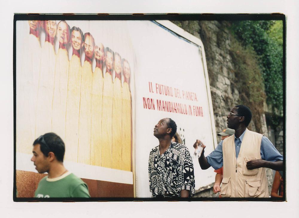 Proteste contro il summit del G8, Genova luglio 2001. 19 luglio, corteo dei Migranti. Dimostranti osservano un manifesto pubblicitario del WWF. Durante i giorni del Genoa Social Forum, molti spazi pubblicitari a Genova vengono acquistati dalle più grosse associazioni ecologiste e per i diritti umani.