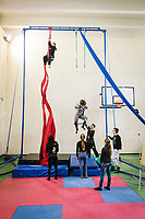 """NAPLES, ITALY - 16 MARCH 2018: Teenagers practice aerial dance and trapeze at """"Il Tappeto di Iqbal"""" (Iqbal's carpet), a non-profit cooperative in Barra, the estern district of Naples, Italy, on March 16th 2018.<br /> <br /> Il Tappeto di Iqbal (Iqbal's Carpet) is a non-profit cooperative founded in 2015 and Save The Children partner since 2015 that operates in the Naple's eastern neighborhood of Barra children in the arts of circus, theater and parkour. It was named after Iqbal Masih, a Pakistani boy who escaped from life as a child slave and became an activist against bonded labor in the 1990s.<br /> Barra, which is home to some 45,000 people, has the highest rate of school dropouts in the Italian region of Campania. Once a thriving industrial community, many of the factories were destroyed in a 1980 earthquake and never rebuilt. The resulting de-industrialization turned Barra into a poor, decaying neighborhood. There are no cinemas, theaters, parks or public spaces in Barra.<br /> The vast majority of children from poor families are faced with the choice of working in the black economy or joining the ranks of the organised crime.<br /> Recently, Save the Children Italy opened a number of educational and social spaces in Barra. The centers, known as Punti Luce, or points of light, aim to help local kids stay out of the ranks of the organised crime and have also become hubs for Iqbal's Carpet to work."""