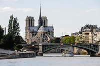 Paris, France. View from a boat on the river Seine. Passing the Notre Dame cathedral. Pont de Sully bridge in the foreground.