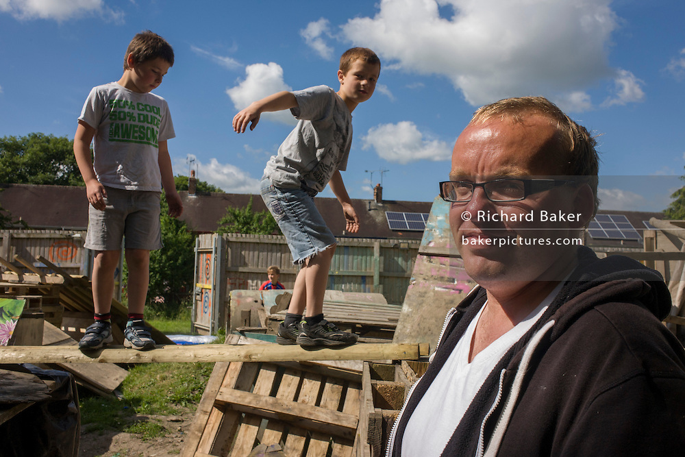 Father and boys in risk averse playground called The Land on Plas Madoc Estate, Ruabon, Wrexham, Wales.