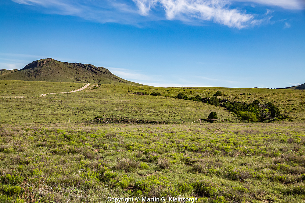 The south side of 6,058 ft. Rabbit Ear Mountain.  The mountain is a remnant of a cinder cone volcano.  Local legend credits the name to a Cheyenne or Comanche chief allegedly killed in battle and buried in a secret cave on the mountain.  Northeast New Mexico.  USA