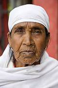 PUTTARPATHI, INDIA - 27th October 2019 - Portrait of senior Indian lady wearing white headscarf at a market in Puttarpathi, Andhra Pradesh, South India