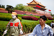 "Woman with face mask cleaning close to the ""The Forbidden City"" which was the Chinese imperial palace from the Ming Dynasty to the end of the Qing Dynasty. It is located in the middle of Beijing, China. Beijing is the capital of the People's Republic of China and one of the most populous cities in the world with a population of 19,612,368 as of 2010."