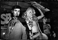 "June 15, 1988:  DJ and club promoter Larry Tee (L) and Drag queen Lahoma Van Zandt on right holding a sign which says ""sex"",  having fun at the Celebrity Club at Tunnel nightclub in New York City, New York."