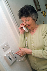 Woman speaking into an entry phone to see who is at the door,