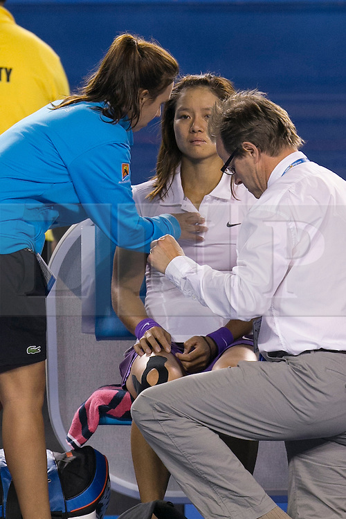 © Licensed to London News Pictures. 26/01/2013. Melbourne Park, Australia. An upset Li Na gets medical attention after falling over during the Womens Final between Victoria Azarenka and Li Na of the Australian Open. Photo credit : Asanka Brendon Ratnayake/LNP